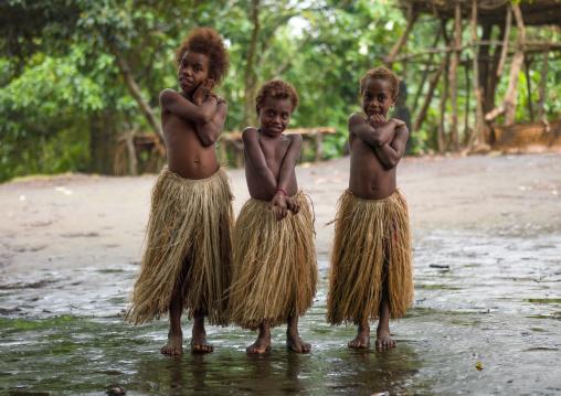 Three girls in traditional grass skirts, Tanna island, Yakel, Vanuatu