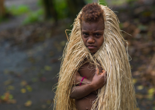 Young girl protecting herself from the rain with a traditional grass skirt, Tanna island, Yakel, Vanuatu
