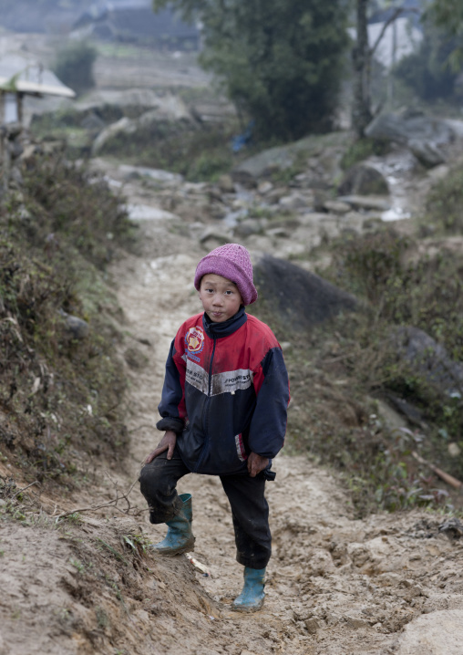 Black hmong boy with a woolly in a muddy path, Sapa, Vietnam