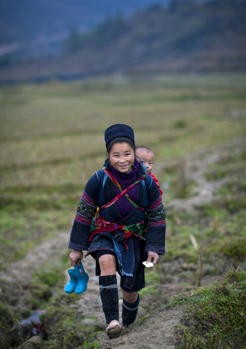 Black hmong girl carrying a baby on her back, Sapa, Vietnam