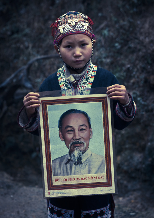 Young red dzao girl showing the portrait of ho chi minh, Sapa, Vietnam