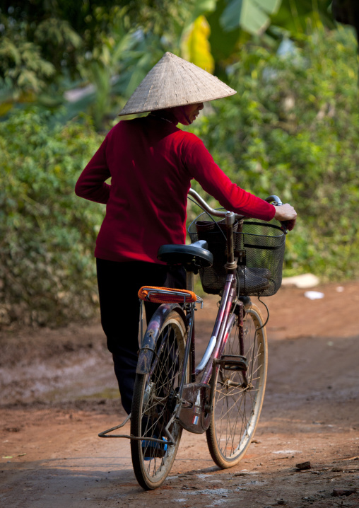 Woman with a sedge hat pushing her bike, Sapa, Vietnam