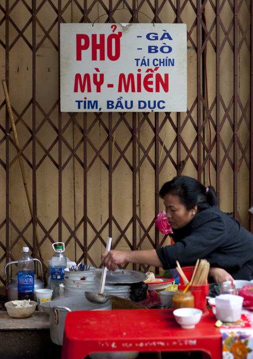 Woman eating in a restaurant, Hanoi, Vietnam