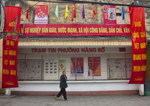 Veiled woman passing by propaganda posters of the communist party fenced with wire, Hanoi, Vietnam