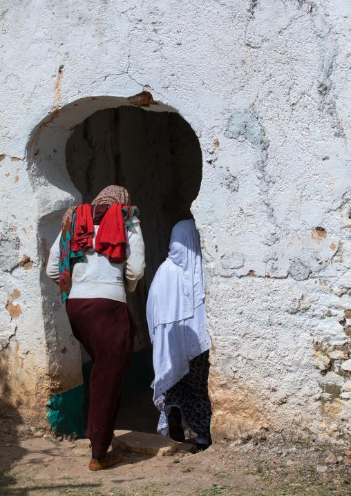 Harari women entering a door in a muslim holy site, Harari Region, Harar, Ethiopia