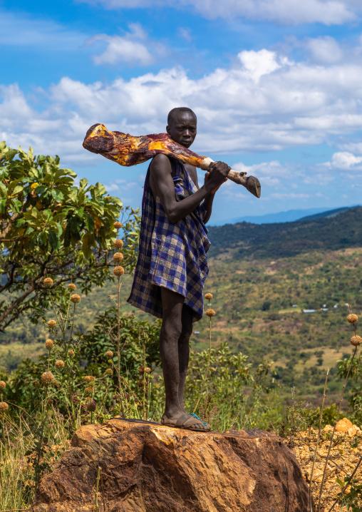 Suri man carrying meat on his shoulder, Omo valley, Kibish, Ethiopia