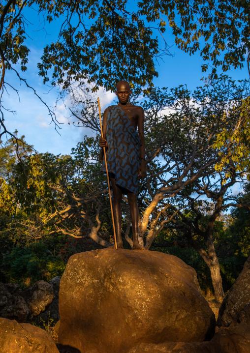 Suri tribe man standing on a giant rock in a sunny light, Omo valley, Kibish, Ethiopia