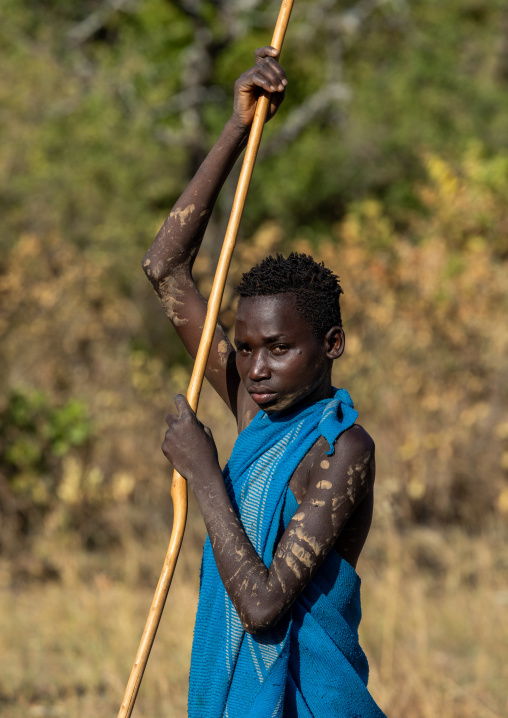 Suri tribe boy with a stick during a donga ritual, Omo valley, Kibish, Ethiopia