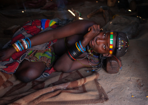 Muhacaona tribe woman resting on her wooden headrest inside her hut, Cunene Province, Oncocua, Angola