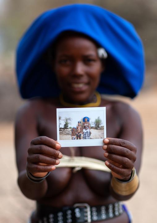 Mucubal tribe woman showing a polaroid, Namibe Province, Virei, Angola