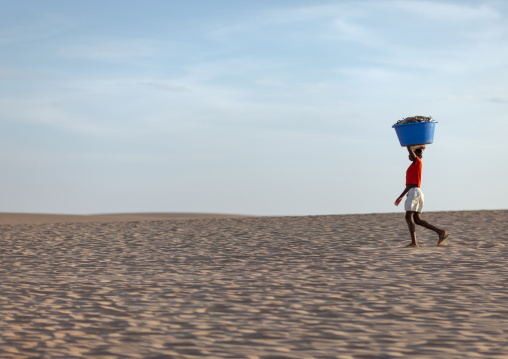Angolan woman carrying fishes on her head along the beach, Namibe Province, Tombua, Angola
