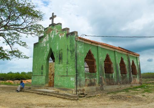 Angolan man sit in front of an abandoned green church, Malanje Province, Calandula, Angola