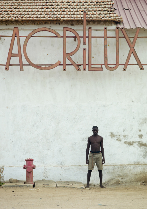 Man In Front Of An Acrilux Old Store In Benguela, Angola