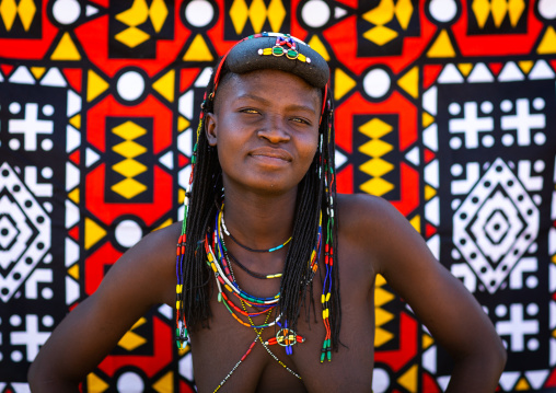 Portrait of a muhakaona tribe woman in front of a colorful printed cloth, Cunene Province, Oncocua, Angola