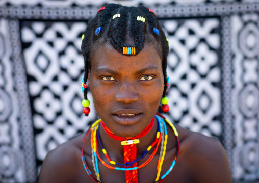 Portrait of a mudimba tribe woman in front of a printed cloth, Cunene Province, Cahama, Angola
