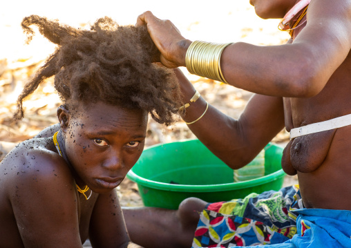 Nguendelengo tribe woman puting oil in her hair to make traditional buns, Namibe Province, Capangombe, Angola