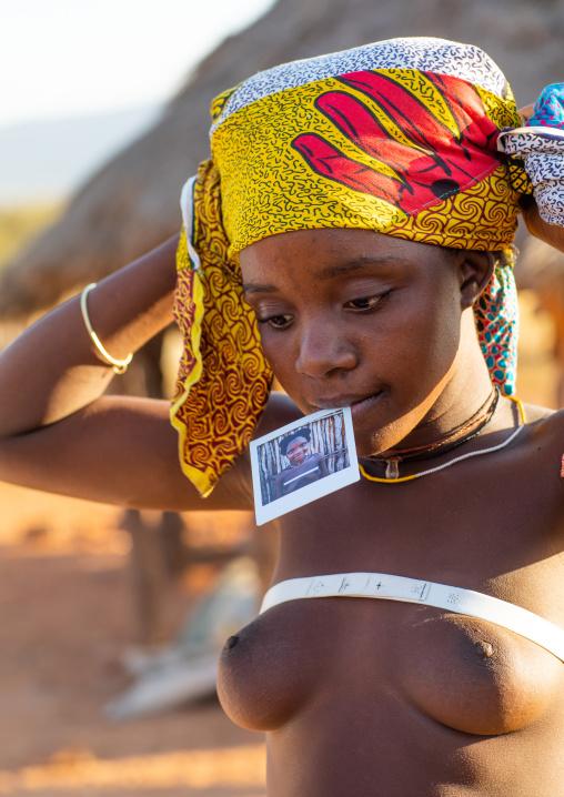 Nguendelengo tribe woman with a Polaroid of herself, Namibe Province, Capangombe, Angola