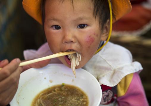 Chinese Baby Eating Noodles, Lijiang, Yunnan Province, China