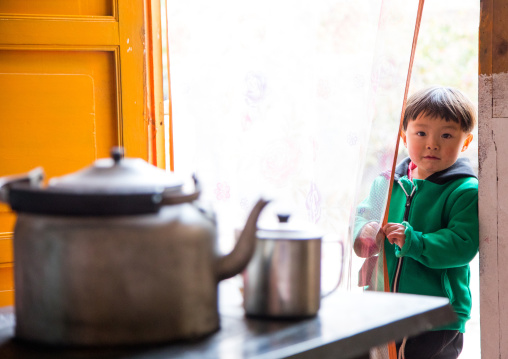 Salar ethnic minority boy at the entrance of his house, Qinghai province, Xunhua, China