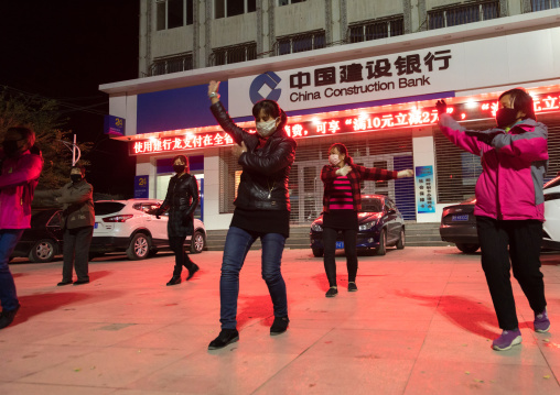 Chinese women dancing in the street at night, Qinghai province, Xunhua, China