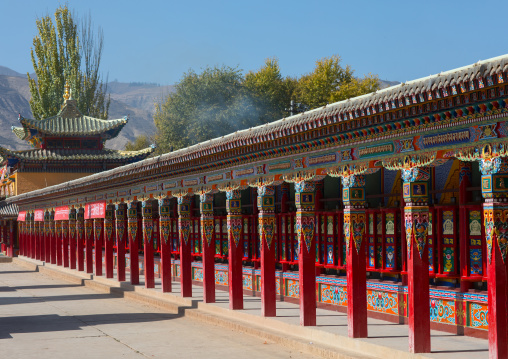 Beautifully painted and adorned prayer wheels in Wutun si monastery, Qinghai province, Wutun, China