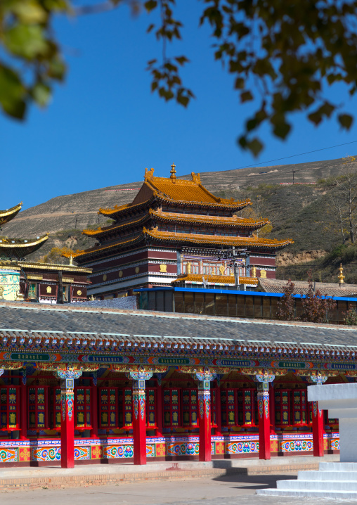 Buddhist temples and beautifully painted prayer wheels in Wutun si monastery, Qinghai province, Wutun, China