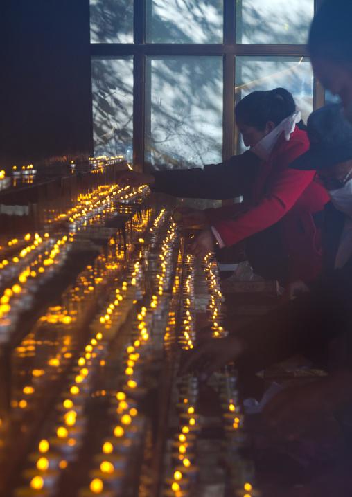Tibetan pilgrims position butter lamps at Rongwo monastery, Tongren County, Longwu, China