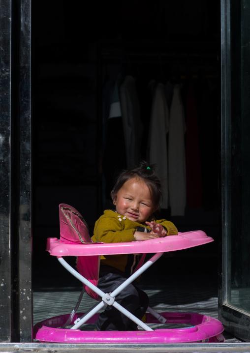 Portrait of a girl sit in her baby walker, Qinghai province, Tsekhog, China
