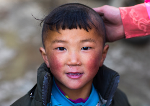 Portrait of a tibetan nomad child with his mother hand on his head, Qinghai province, Tsekhog, China