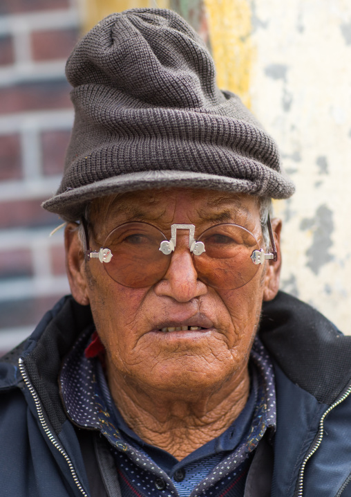 Tibetan man with sunglasses during a pilgrimage in Labrang monastery, Gansu province, Labrang, China