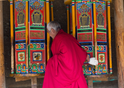 Tibetan monk turning huge prayer wheels in Labrang monastery, Gansu province, Labrang, China