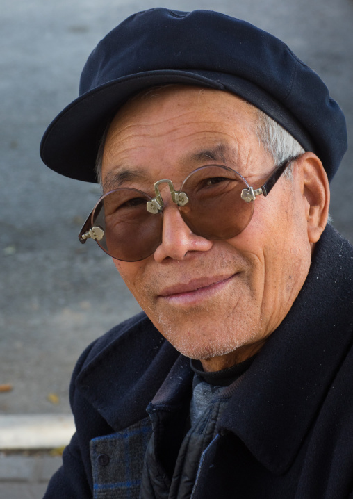 Old man with traditional sunglasses and cap, Gansu province, Linxia, China