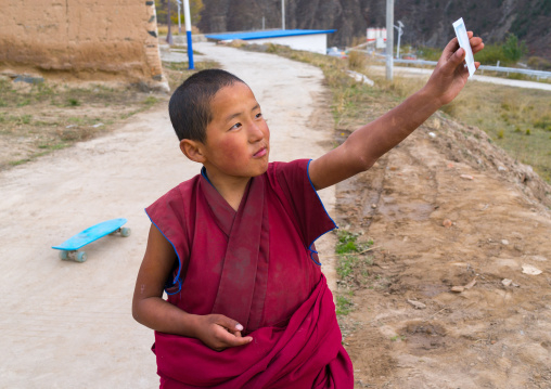 Young tibetan monk holding a polaroid in his hand in Lhachub monastery, Gansu province, Lhachub, China