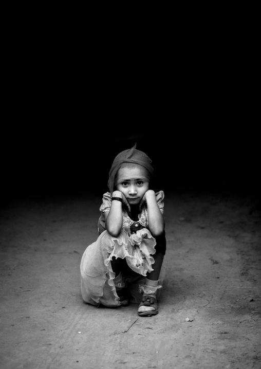 Young Uyghur Girl Squatting Alone In The Street, Yarkand, Xinjiang Uyghur Autonomous Region, China