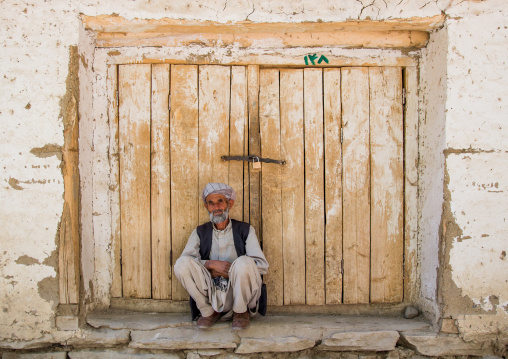 Old man in front of a closed door in the market, Badakhshan province, Ishkashim, Afghanistan