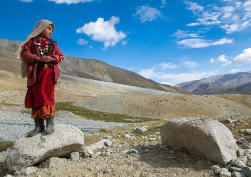 Wakhi nomad girl standing on a rock, Big pamir, Wakhan, Afghanistan