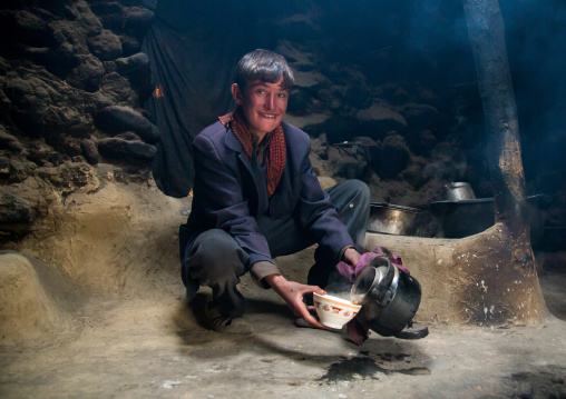 Wakhi teenage boy preparing salty milk tea inside his house, Big pamir, Wakhan, Afghanistan