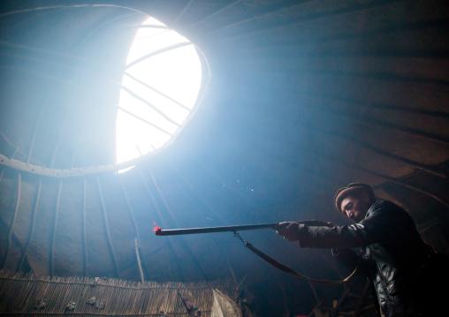 Wakhi nomad man with his gun inside his yurt, Big pamir, Wakhan, Afghanistan