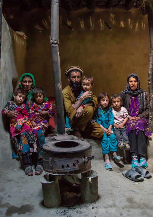Afghan family in front of a stove, Badakhshan province, Khandood, Afghanistan