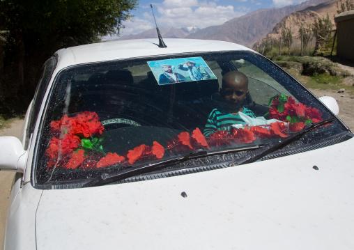 Afghan boy inside a car with ahmad shah massoud poster on the windshield, Badakhshan province, Khandood, Afghanistan