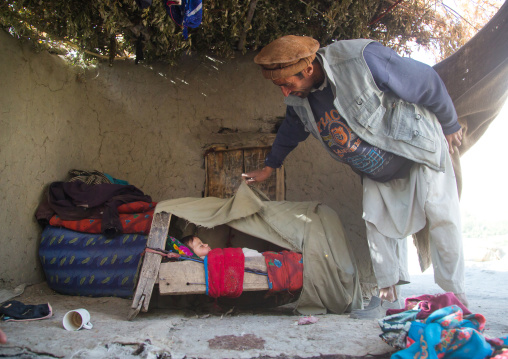 Father looking at his baby sleeping in a craddle, Badakhshan province, Qazi deh, Afghanistan