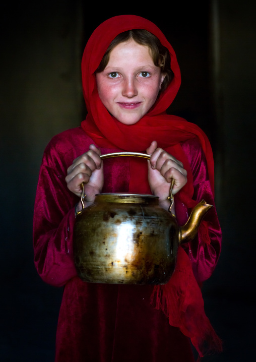 Portrait of an afghan girl with pale skin wearing red clothes and holding a tea pot, Badakhshan province, Khandood, Afghanistan