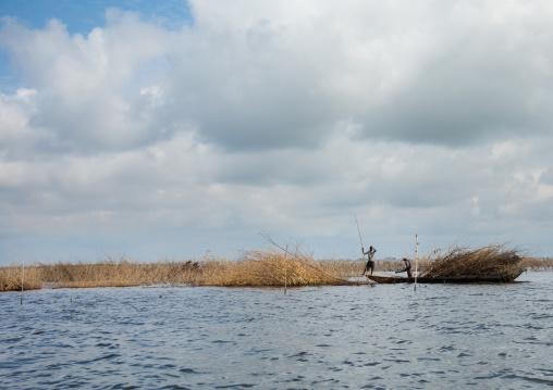 Benin, West Africa, Ganvié, farmers poling boat on nokoue lake near ganvie stilt village