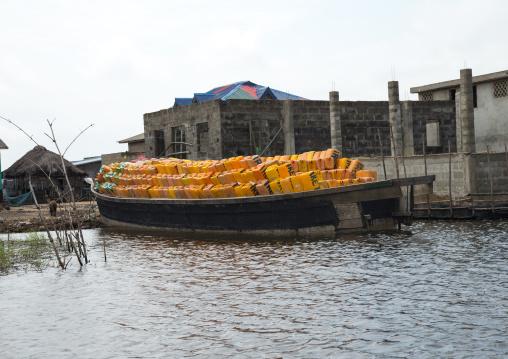 Benin, West Africa, Ganvié, boat carrying oil jerrycans on lake nokoue