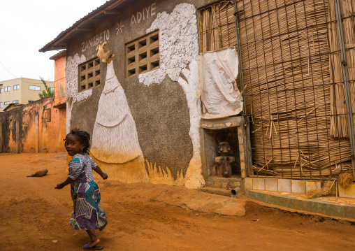 Benin, West Africa, Porto-Novo, young girl passing in front of zangbeto adiye temple