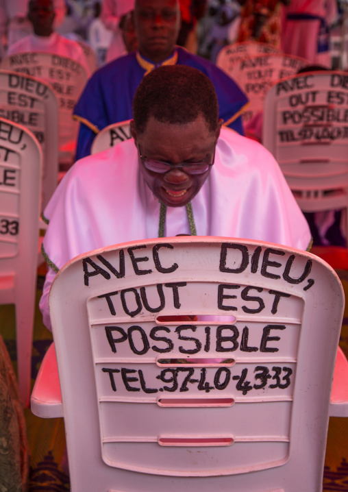 """Benin, West Africa, Ganvié, celestial church of christ men praying in front of a chair with """"with god everything is possible"""" slogan"""