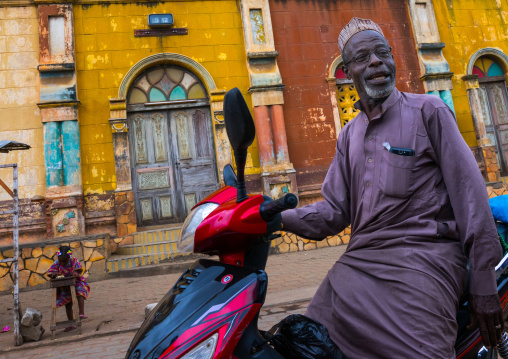 Benin, West Africa, Porto-Novo, old muslim man on a scooter in front of the multicoloured great mosque