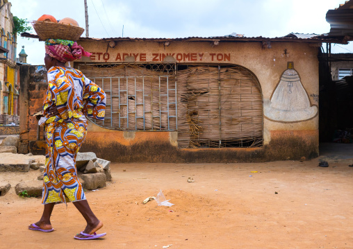 Benin, West Africa, Porto-Novo, woman passing in front of a voodoo temple