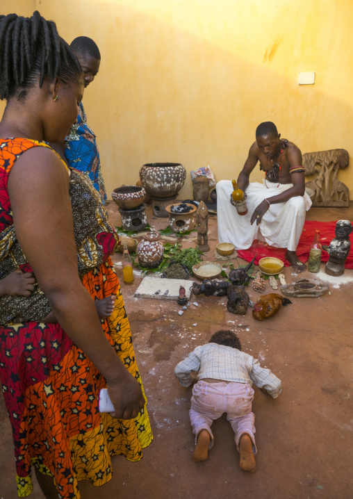 Benin, West Africa, Bonhicon, a child bowing in front of kagbanon bebe voodoo priest during a ceremony