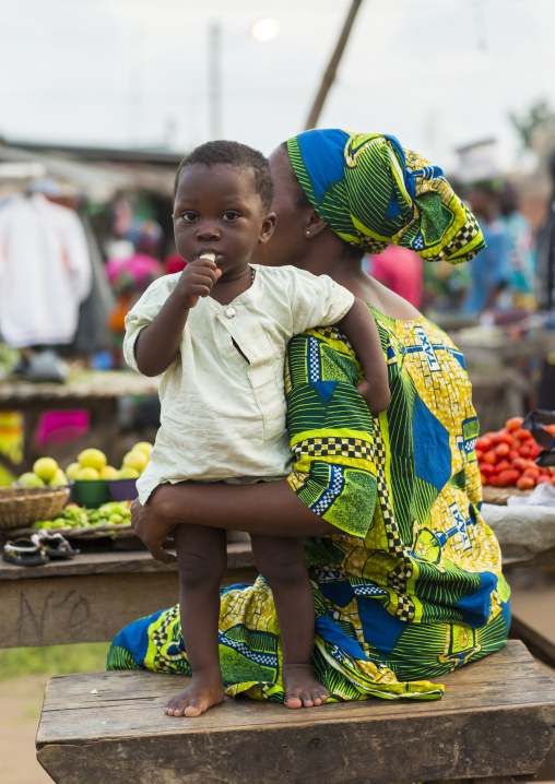 Benin, West Africa, Porto-Novo, child with his mother eating a banana in a market